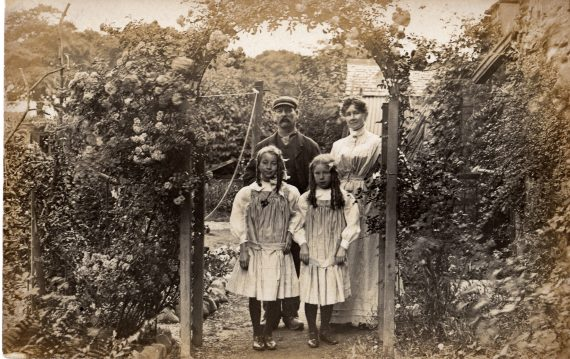 Black-and-white postcard of garden with family, late nineteenth century